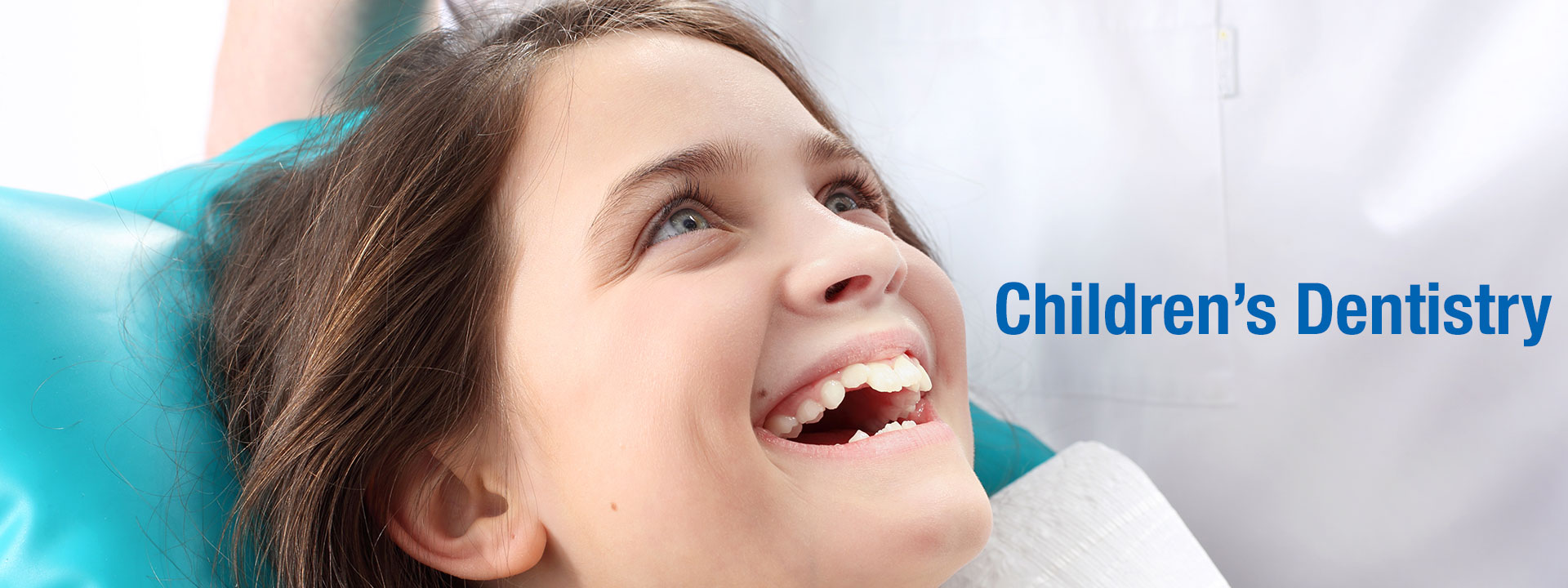 children's dentistry - child sitting on a dentist chair and smiling